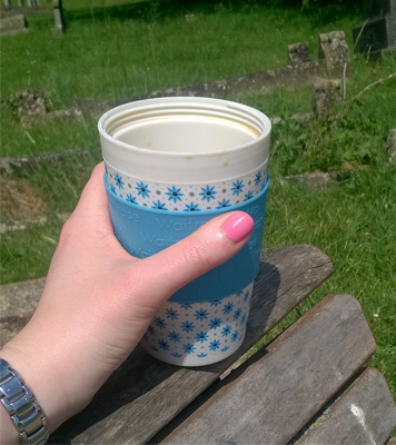 Reusable coffee cup, on a bench on a sunny day, thinking about non-bookish items